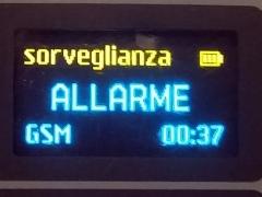 Una microspia GSM e'  in funzione  e sul display  si legge in grande l ascritta ALLARME , sotto il tipo di segnale ( GSM ) e in basso a sinistra l'orario